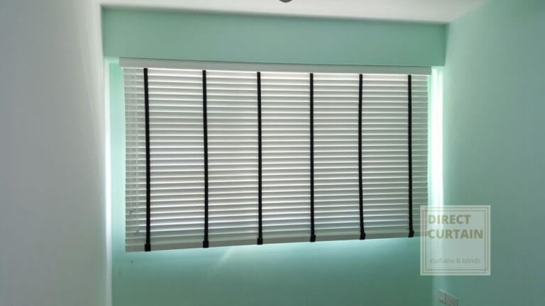 White venetian blinds in teal room