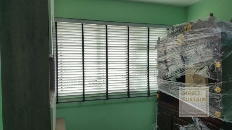 White venetian blinds in green room